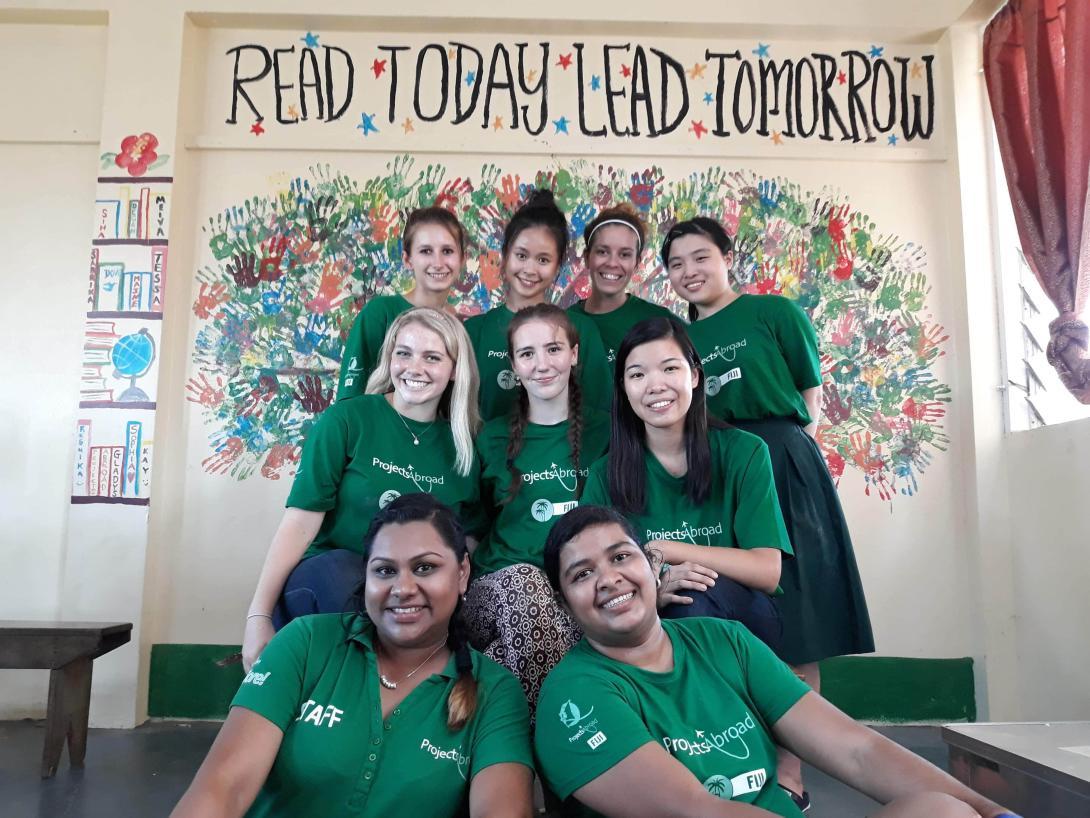 Estudiantes en un voluntariado para adolescentes posando después de terminar un mural para promover la lectura en Fiyi.